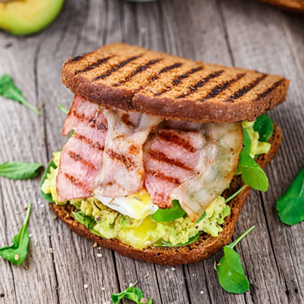 Avocado, bacon and eggs on toast